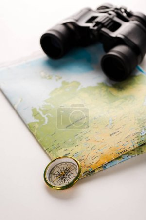 golden compass near map and binoculars on white