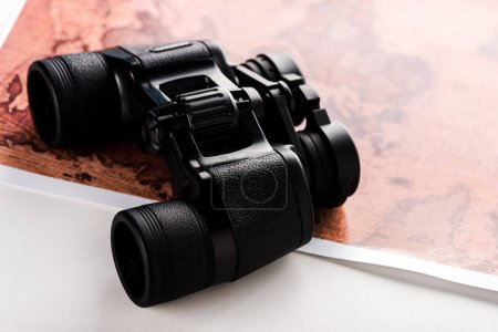 Photo for Selective focus of black binoculars on map on white - Royalty Free Image