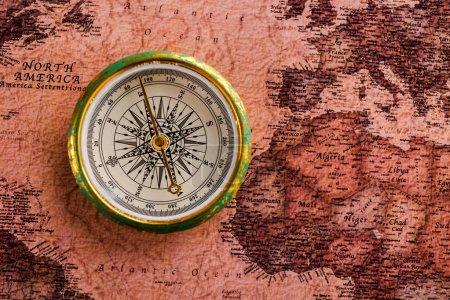 Photo pour Vue du dessus de la boussole dorée près de la carte - image libre de droit