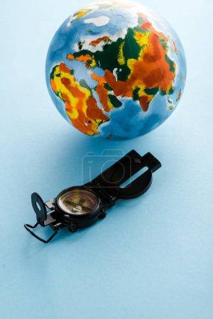 retro compass near colorful globe on blue