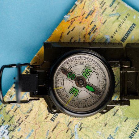 Photo for Close up of black compass near map on blue - Royalty Free Image