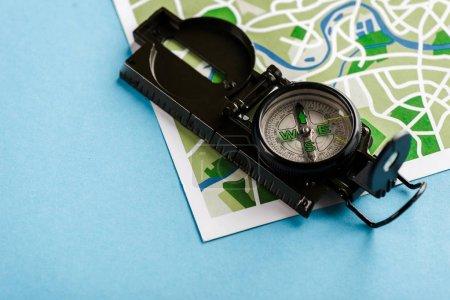 Photo pour Boussole rétro et noire sur la carte sur bleu - image libre de droit