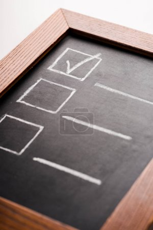 close up of chalk board with check mark isolated on white