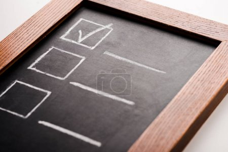 close up of chalk board with tick in checklist isolated on white