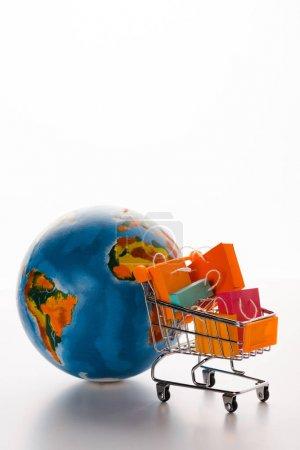 Photo pour Mise au point sélective de chariots jouets avec sacs à provisions près du globe sur blanc, concept de commerce électronique - image libre de droit