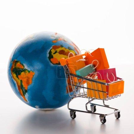 Photo pour Chariot d'achat de jouets avec sacs à provisions près du globe sur blanc, concept e-commerce - image libre de droit