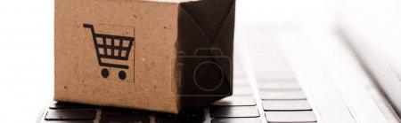 Photo pour Photo panoramique d'une boîte de carton pour jouets sur un clavier d'ordinateur portable isolée sur un clavier blanc, concept de commerce électronique - image libre de droit