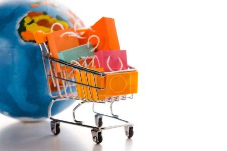 Photo pour Chariot jouet avec petits sacs près du globe sur blanc, concept e-commerce - image libre de droit