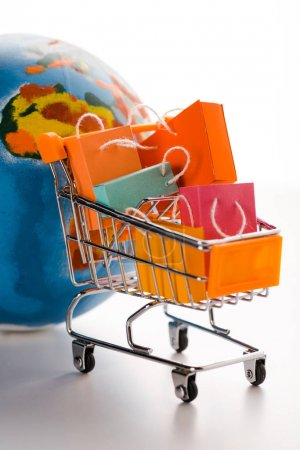 Photo for Toy shopping cart with small colorful shopping bags near globe on white, e-commerce concept - Royalty Free Image