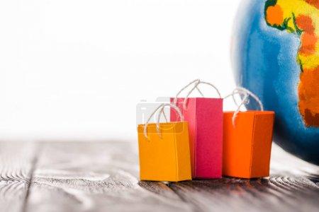 Photo pour Sacs jouets colorés près du globe sur table, isolés sur blanc, concept de commerce électronique - image libre de droit