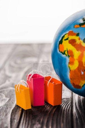 Photo pour Sacs jouets près du globe sur table isolés sur blanc, concept de commerce électronique - image libre de droit
