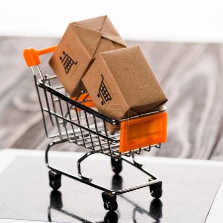 Photo for Close up of toy shopping cart with small boxes on digital tablet, e-commerce concept - Royalty Free Image