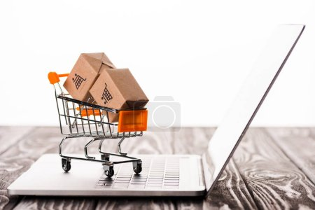 selective focus of toy shopping cart with small carton boxes on laptop isolated on white, e-commerce concept