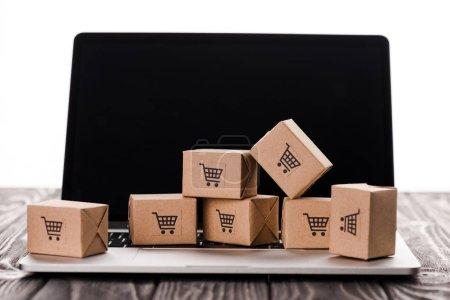 Photo pour Boîtes à jouets sur ordinateur portable avec écran vierge isolées sur écran blanc, concept de commerce électronique - image libre de droit