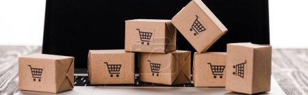 Photo pour Plan panoramique de boîtes en carton de jouets sur ordinateur portable avec écran blanc isolé sur blanc, concept de commerce électronique - image libre de droit