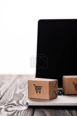 Photo pour Mise au point sélective de petites boîtes en carton sur ordinateur portable avec écran vierge sur table isolée sur blanc, concept de commerce électronique - image libre de droit