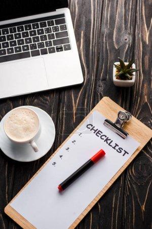 Photo pour Vue du haut de l'ordinateur portable près du presse-papiers avec liste de contrôle, plante, stylo marqueur rouge et tasse de café sur la table, concept de commerce électronique - image libre de droit