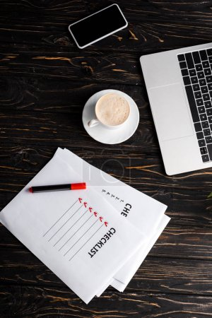 Photo pour Top view of gadgets near papers with checklist, red marker pen and cup of coffee on table, e-commerce concept - image libre de droit