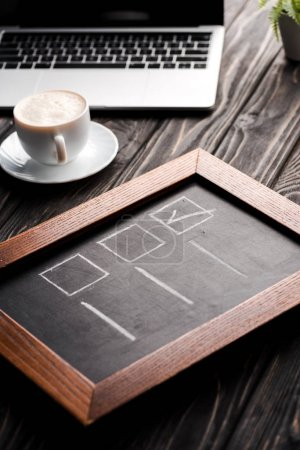 selective focus of chalk board with checklist near cup of coffee and laptop on table, e-commerce concept