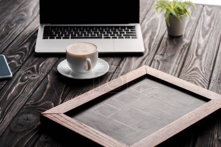selective focus of chalk board near cup of coffee and laptop on table, e-commerce concept
