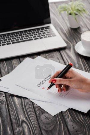 Photo pour Crochet représentant une femme d'affaires tenant un marqueur rouge près d'une liste de contrôle, une tasse et un ordinateur portatif sur une table, concept de commerce électronique - image libre de droit