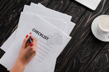 Foto de Vista superior del bolígrafo marcador de mujeres de negocios cerca de la lista de verificación y taza de café en la mesa. - Imagen libre de derechos