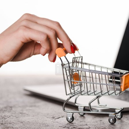Photo pour Close up of woman holding toy shopping cart near laptop isolated on white, e-commerce concept - image libre de droit