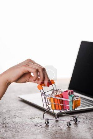 Photo pour Croustillant vue d'une femme tenant un chariot d'achat de jouets avec de petits sacs d'achat près d'un ordinateur portable isolé sur blanc, concept de commerce électronique - image libre de droit