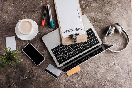 Photo pour Top view of gadgets near credit cards, cup, plant, headphones and clipboard with checklist, e-commerce concept - image libre de droit