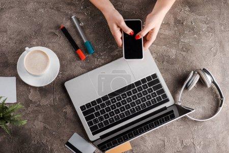 Photo pour Top view of woman holding smartphone near laptop, cup of coffee, plant, headphones and credit cards, e-commerce concept - image libre de droit