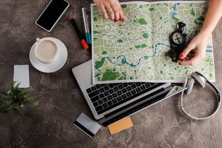 Photo pour Vue d'en haut de la femme près de la carte, boussole, cartes de crédit et gadgets, concept de commerce électronique, concept de commerce électronique - image libre de droit