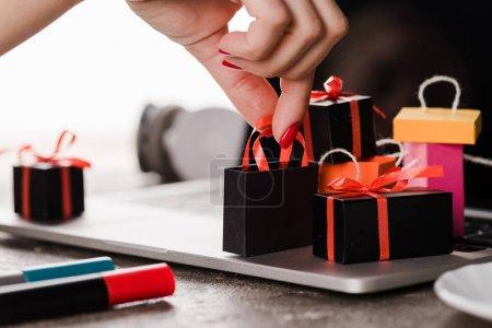 Photo pour Crochet vue d'une femme touchant des sacs à jouets près d'un ordinateur portatif sur blanc, concept de commerce électronique - image libre de droit