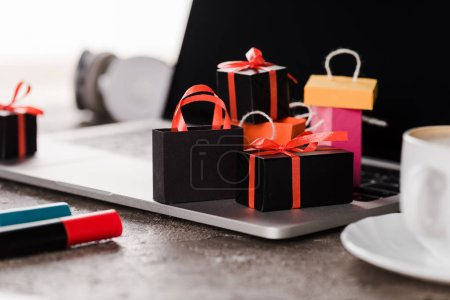 Photo for Selective focus of shopping bags near laptop, cup and marker pens on white, e-commerce concept - Royalty Free Image