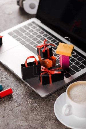 Photo pour Foyer sélectif des sacs à provisions près de l'ordinateur portable, tasse de café et marqueurs stylos, concept e-commerce - image libre de droit