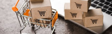 Photo for Panoramic shot of toy shopping cart with small carton boxes near laptop, e-commerce concept - Royalty Free Image