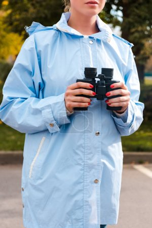 Photo for Cropped view of woman in blue raincoat holding binoculars - Royalty Free Image