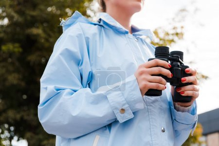 Photo pour Vue recadrée de la femme en imperméable tenant des jumelles à l'extérieur - image libre de droit