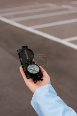 Photo for Cropped view of woman holding compass near road - Royalty Free Image