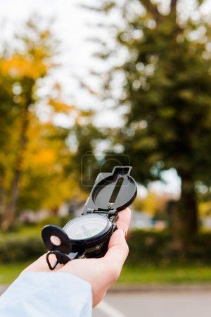 Photo pour Vue recadrée de la femme tenant boussole dans le parc automnal - image libre de droit