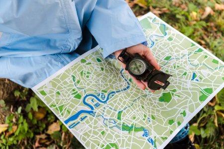 Ausgeschnittene Ansicht des Reisenden, der Karte und Kompass draußen hält