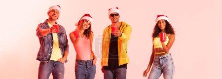 Photo pour Plan panoramique d'amis multiculturels heureux dans des chapeaux Santa tenant des tasses en plastique sur rose - image libre de droit