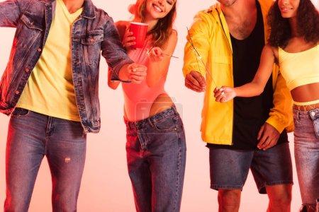 Foto de Happy multicultural friends with sparklers standing isolated on pink - Imagen libre de derechos