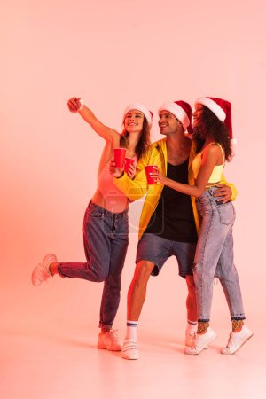 Photo pour Happy girl taking selfie with multicultural friends in santa hats on pink - image libre de droit