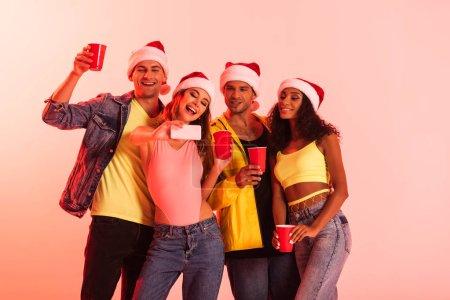 Photo pour Femme gaie prenant selfie avec des amis multiculturels dans santa chapeaux isolés sur rose - image libre de droit