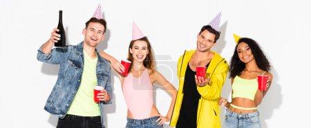 Photo pour Photo panoramique d'amis multiculturels heureux en casquettes tenant des tasses en plastique sur du blanc - image libre de droit