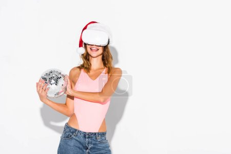 Photo for Happy girl in santa hat holding holding disco ball on white - Royalty Free Image