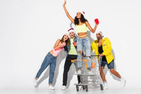 Photo for Cheerful african american girl waving hand in shopping cart near friends with plastic cups on white - Royalty Free Image