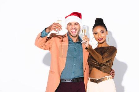 Photo pour Gai afro-américain fille tenant verre de champagne près de l'homme dans santa chapeau sur blanc - image libre de droit
