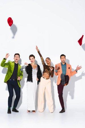 Photo pour Des amis multiculturels heureux et élégants, portant des chapeaux de santa aérienne et des verres de champagne blancs - image libre de droit