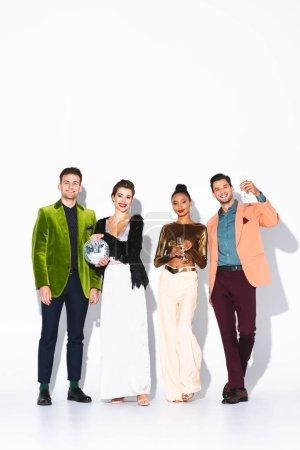 Foto de Amigos multiculturales felices y de moda sosteniendo copas de champán y bola disco en blanco - Imagen libre de derechos